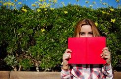 Den charmiga unga kvinnan med rosa färger bokar rymt upp nästan hennes framsida royaltyfri bild