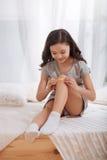 Den charmiga ungen som sätter bindemedel, förbinder på knä hemma royaltyfria foton