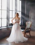 Den charmiga utmärkta damen blev bruden, flicka med blont samlat hår försöker på att gifta sig den chic vita lyxiga ljusa klännin royaltyfria foton