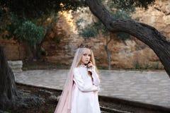 Den charmiga vita häxaforetelleren står i en mystisk magisk skog i en bröllopsklänning med en skyla och en krona royaltyfri fotografi