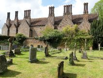 Den Chenies mangårdsbyggnaden, en Tudor Grade listade jag byggnad, med den kyrkliga kyrkogården i förgrund royaltyfri bild