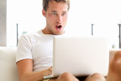 Chockad förvånad man som ser bärbar datordatoren Arkivfoton
