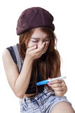 Den chockade flickan rymmer graviditetstestet royaltyfri fotografi