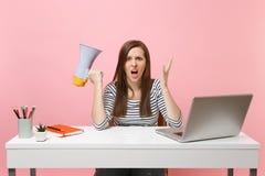 Den chockade ilskna kvinnan som skriker fördelande händer som rymmer megafonen, sitter och arbetar på det vita skrivbordet på kon royaltyfri foto