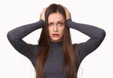 Den chockade kvinnan rymmer hennes händer på huvudet arkivbild