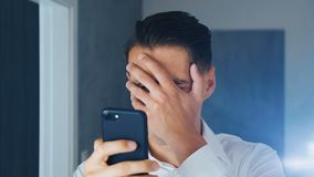 Den chockade mannen såg ett otrevligt meddelande på en smartphone En man gör facespalm efter ett meddelande beskådas på en smartp lager videofilmer