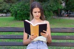 Den chockade och förvånade kvinnan rymmer en bok och har misshagit blick arkivbild