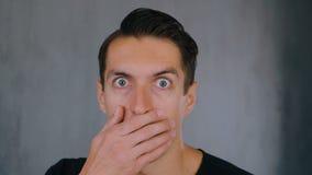 Den chockade och förvånade mannen tar av hans exponeringsglas och blickar på kameran i överraskning lager videofilmer