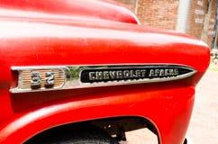 Den Chrome logoen av den röda klassiska Chevrolet apache pickupet för parkerar garnering på förbudsmällen Khen Arkivfoton