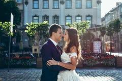 Den Closr-up bröllopståenden av det härligt le att gifta sig krama och slappt att trycka på precis noses utomhus- Arkivfoto