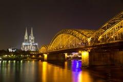 Den Cologne domkyrkan och Hohenzollern överbryggar på natten, Cologne (Koeln), Tyskland Royaltyfria Bilder