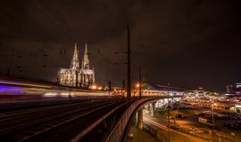 Den Cologne domkyrkan på natten med det S-Bahn drevet Arkivfoton
