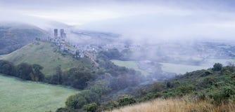 Den Corfe slotten fördärvar i morgonmisten arkivfoto