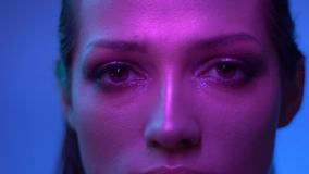 Den Cosmical modemodellen i violetta neonljus håller ögonen på fast och stänger ögon långsamt för att visa för att blänk lager videofilmer