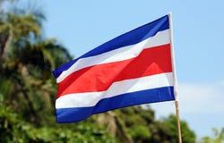 Den Costa Rica flaggan som vinkar på den Manuel Antonio nationalparkstranden i mest härlig stränder i världen, surfare sätter på  royaltyfria bilder