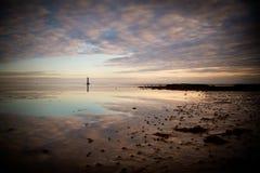 Den Cranfield fyren som solen ställer in med reflexion i havet Royaltyfri Foto