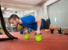 Den Crossfit konditionmannen skjuter ups Kettlebells liggande armhävningövning Royaltyfri Fotografi