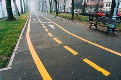 Den cykelgränder och trottoaren med parkerar bänken Arkivfoton