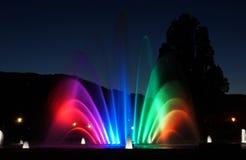 Den dåliga kissingebrunnsorten parkerar på natten med den färgade springbrunnen Arkivfoton