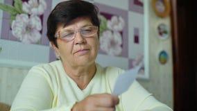 Den Defocused höga gamla kvinnan i glasögon som kontrollerar kostnader av dagstidningen, uppta som omkostnad hemma lager videofilmer