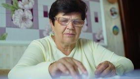 Den Defocused höga gamla kvinnan i glasögon som kontrollerar kostnader av dagstidningen, uppta som omkostnad hemma stock video