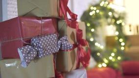 Den Defocused oerhörda sikten på slågna in julgåvagåvor traver i träd för nytt år i dekorerat festligt atmosfärrum arkivfilmer
