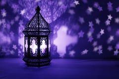 Den dekorativa arabiska lyktan med bränningstearinljuset som glöder på natten och blänker stjärnor, formade bokehljus festligt royaltyfria foton