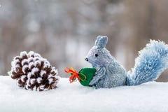 Den dekorativa ekorren i snön som rymmer en påse med gåvor, är därefter en klumpa sig i snön, Royaltyfria Bilder