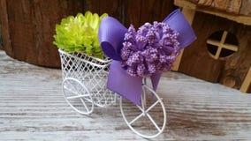 Den dekorativa hemtrevliga cykeln med korgen av blommor och lilor bugar Royaltyfri Fotografi