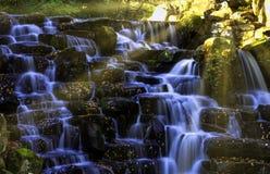 Den dekorativa kaskadvattenfallet med den synliga solen rays - Virginia Water, Surrey, Förenade kungariket royaltyfria foton