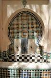 Den dekorativa offentliga vattendispensoren enwrapped i skuggor sitter i den gamla Medinaen av Fez, Marocko Arkivbilder