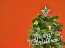 Den dekorerade julgranen med glad jul undertecknar på röd väggbakgrund Arkivbilder