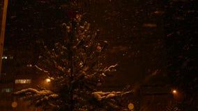 Den dekorerade julgranen står på gatan på natten, i ett snöfall, en röd stjärna på överkanten av huvudet lager videofilmer