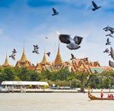 Den dekorerade pråm ståtar förbi den storslagna slotten på Chao Phraya River Arkivbilder
