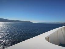 Den delade skärmen av blå himmel, avlägsna öar, det djupblå havet och vit sänder i det Aegean havet, Grekland arkivbild