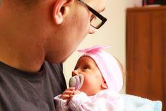 Den delikata fadern som rymmer hans nyfött, behandla som ett barn Arkivfoton