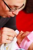 Den delikata fadern som rymmer hans nyfött, behandla som ett barn Royaltyfri Bild