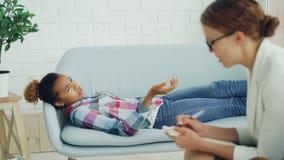 Den deprimerade afrikansk amerikanflickan talar till psykologen som ligger på soffan och talar, medan terapeuten i exponeringsgla stock video