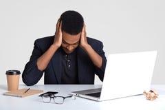 Den deprimerade svarta mannen håller blick ner, håller båda händer på huvudet, välter för att fortsätta att arbeta, har på proble arkivfoton