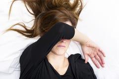 Den deprimerade unga kvinnan ligger i hennes säng som täcker henne ögon arkivbild