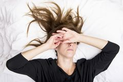 Den deprimerade unga kvinnan ligger i hennes säng som täcker henne ögon arkivbilder