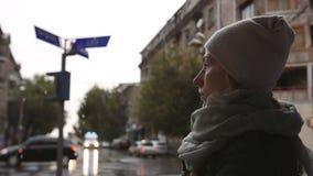 Den deprimerade unga kvinnan ser ambulansbilen som går på gatavägen på en regnig afton i staden stock video