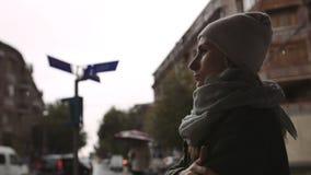 Den deprimerade unga kvinnan ser gatan på en regnig afton i staden arkivfilmer