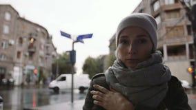 Den deprimerade unga kvinnan ser gatan på en regnig afton i staden stock video