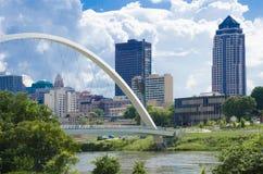 Den Des Moines flodfördämningen och den i stadens centrum fot- bron fotografering för bildbyråer