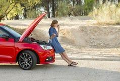 Den desperata förvirrade kvinnan strandade med bruten olycka för krasch för bilmotor som kallar på mobiltelefonen Royaltyfri Fotografi