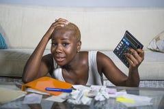 Den desperata och stressade svarta afro amerikanska kvinnan med räknemaskin- och skrivbordsarbetebankrörelsen i finans för spänni royaltyfri foto