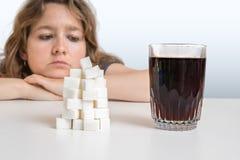 Den diabetiska kvinnan ser på exponeringsglas med coladrinken och högen av socker äta för begrepp som är sjukligt arkivfoto