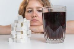 Den diabetiska kvinnan ser på exponeringsglas med coladrinken och högen av socker äta för begrepp som är sjukligt arkivbild