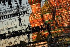 Den diagonala sikten på arbetare på etappkonstruktion jämnar på den röda fyrkanten för Moskva framme av den Vasiliy Blazhenniy do Arkivfoton